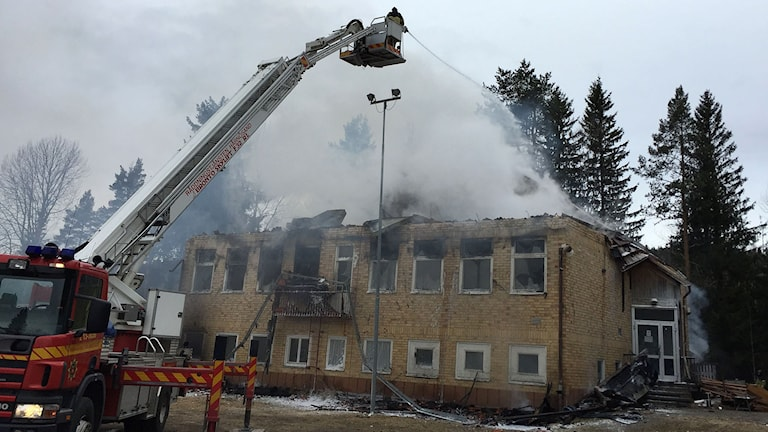 Kraftig rök stiger ur ruinerna efter branden i gamla skolan i Viksjö som var planerad att bli flyktingboende för barn. Foto: Niklas Axelsson/SR