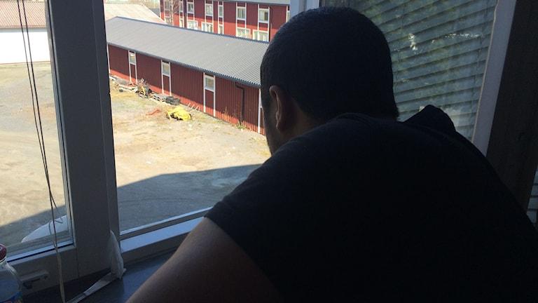 Mustafa 26 år tittar ut över gården från ett fönster. Foto: Pether Öhlén/Sveriges Radio