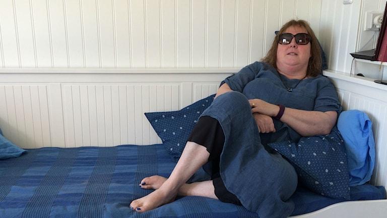 Cecilia Ekhem i blå klänning vilar i sin blå soffa. Hon lider av den neurologiska sjukdomen ME. Foto: Ingrid Engstedt-Edfast