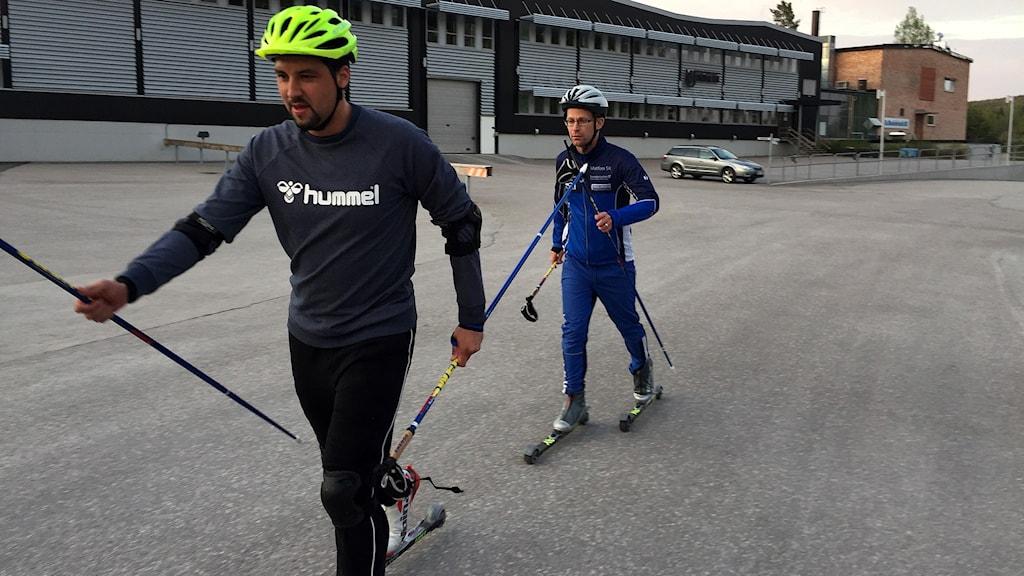 Jhon Acevedo och tränaren Peter Blomqvist tätt bakom på rullskidor. Foto: Niklas Axelsson/SR