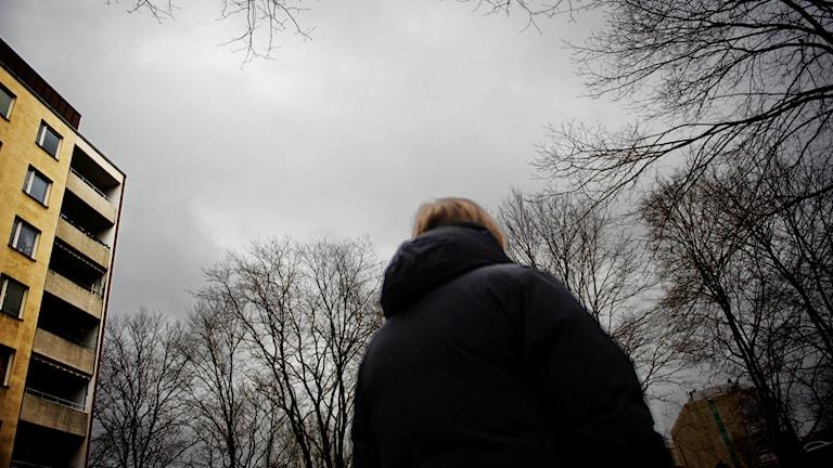 En kvinna står med ryggen till kameran