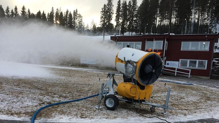 En av snökanonerna vid Hallstaberget tillverkar konstgjord snö som sprutas ut i en snömoln. Foto: Lennart Sundwall/Sveriges Radio