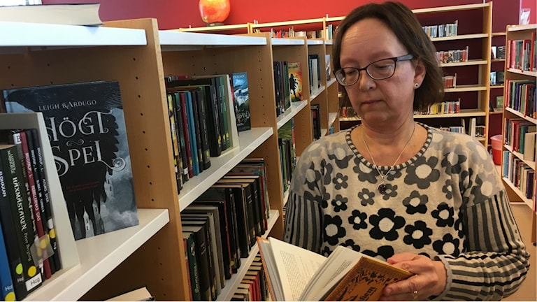 Charlotte Andersson läser ur en bok och hon är bibliotikarie på Timrå bibliotek.
