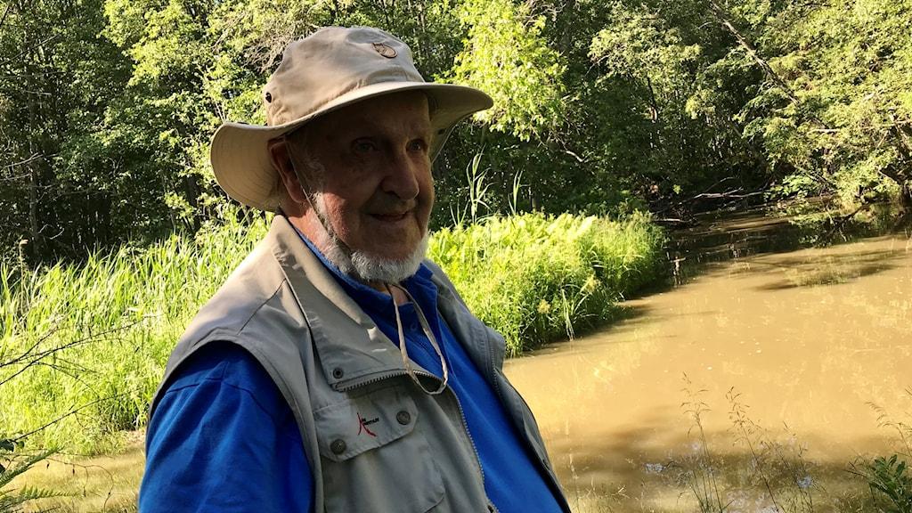 Lars-Göran Olofsson står bredvid ån. Han har fiskat där hela livet. Han är en man på 86 år och har grå skepparkrans. Han är klädd i beige fiskehatt, beige fiskeväst och under det har han en kornblå pikéskjorta. Foto: Alexander Arvidsson/Sveriges Radio