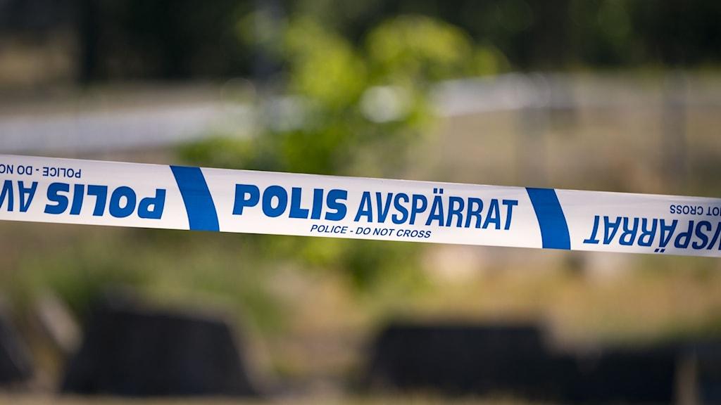 Blåvitt band med polis skrivet