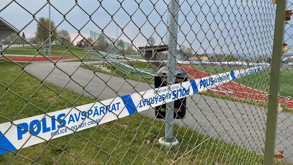 Ett galler runt en idrottsplats där det sitter polis-avspärrningsband.