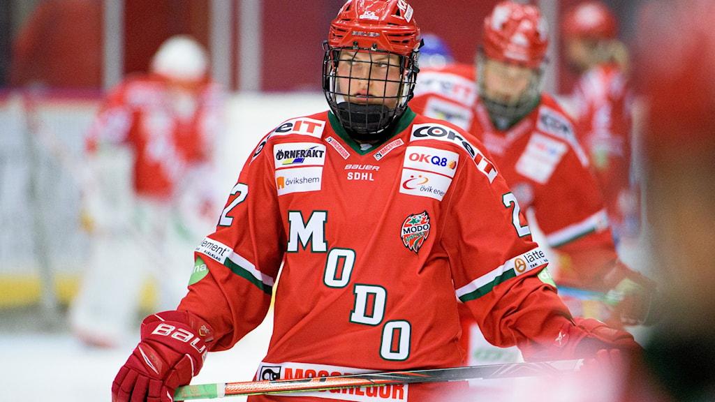 Rödklädd hockeyspelare åker runt i rinken.