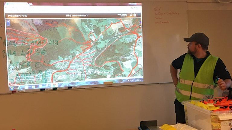 Mikael Stenberg tittar på en tavla där de har kartbild över sökområdet