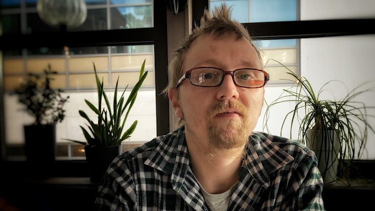 Per Tjärnström är 33 år och förtidspensionär. Han sitter här på ett café i centrala Örnsköldsvik och tittar in i kameran. Han är klädd i svart-vit rutig skjorta, han har glasögon med rödbruna bågar, kort rödblont hår och ojämnt skägg runt munnen i samma färg. Foto: Alexander Arvidsson/Sveriges Radio