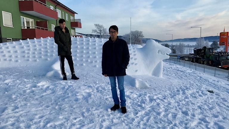 Sayed Mohammad Ali Mosavi och tolken står vid snöskulptur som ser ut som en krokodil