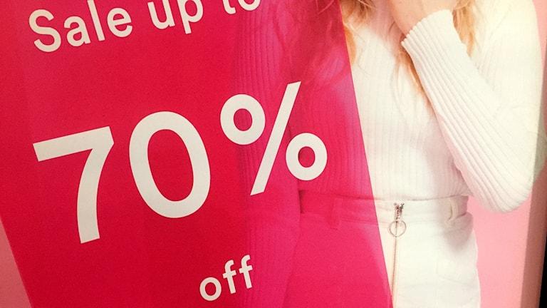 """En stor röd affisch med texten """"Sale up to 70% off"""" i ett skyltfönster. Foto: TullaMaja Fogelberg/Sveriges Radio"""