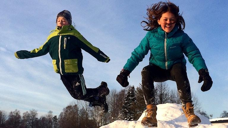 Vincent Claesson och Maja Olsson som tävlar för 5A på Bergsåkers skola hoppar ner från ett snöberg på skolgården. Foto: Ann Viberg