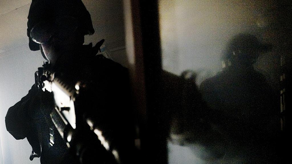 En militär håller ett automatvapen i mörker under en övning.  Foto: Caroline Tibell/SvD/TT