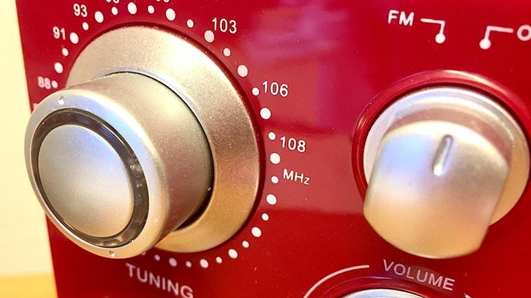 Närbild på röd radioapparat med tuningvred och på- och avknapp. Foto: Karin Lönnå/Sveriges Radio