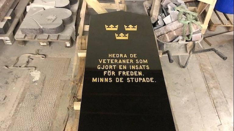 Svart minnessten med guldtext Hedra de veteraner som gjort en insats för freden. Minns de stupade.
