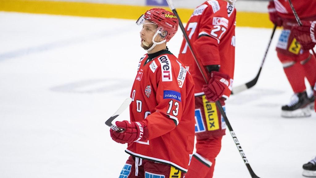Rödklädd hockeyspelare åker med klubban högt hållen och en deppig min.