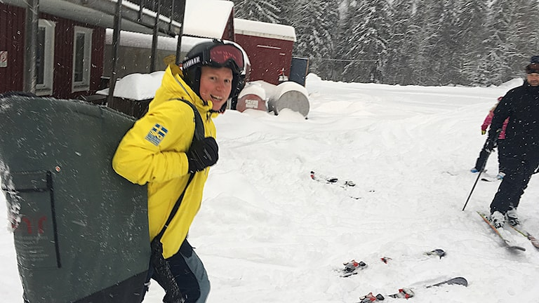 Sandra Näslund i gul jacka och hjälm bär utrustning i en bag över axeln. Foto: Peter Hansson/Sveriges Radio