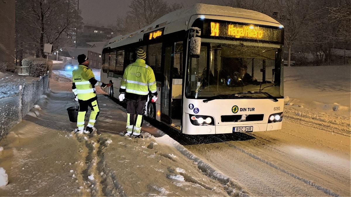 En stillastående buss i den branta Stadsbacken i Sundsvall får undsättning i snöyran av två medarbetare från Nobina.