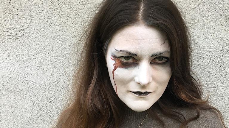 TullMaja färdigsminkad med vitt ansikte, svarta markerade ögon, svarta läppar och blod rinnande från höger öga. Foto: Ann-Charlotte Carlsson/Sveriges Radio