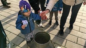 Moa i Timrå lägger pengar i bössan under Världens Barn 2017.