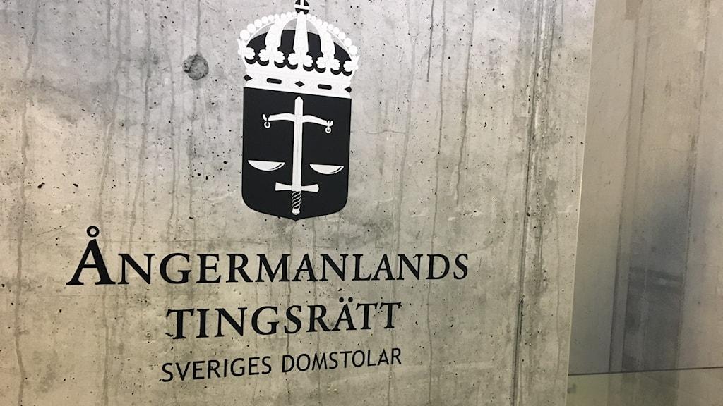 Ångermanlands tingsrätts emblem tryckt med svart färg mot en grå betongvägg.
