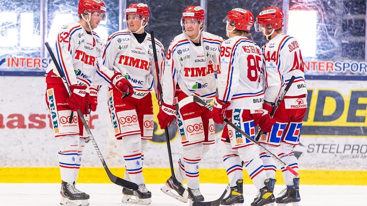 Ishockeyspelare med vit/röda tröjor.