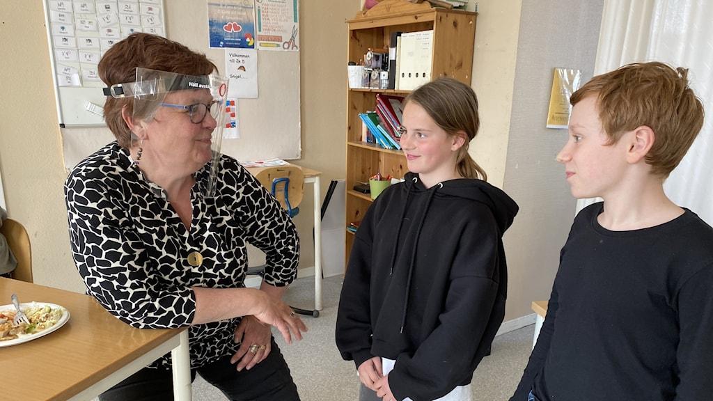 Lärare med visir och två elever vid skolbänk.