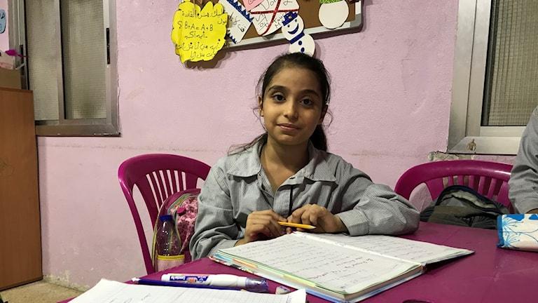 Amina Al Laham 9 år sitter vid ett plastbord med uppslagna skolböcker.