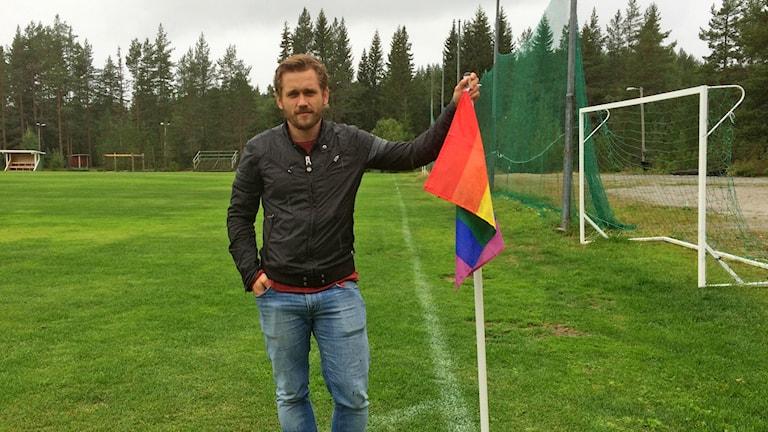 Mats Falck på fotbollsplanen i Gottne lutandes mot en regnbågsflagga. Foto: Anton Kårén/Sveriges radio