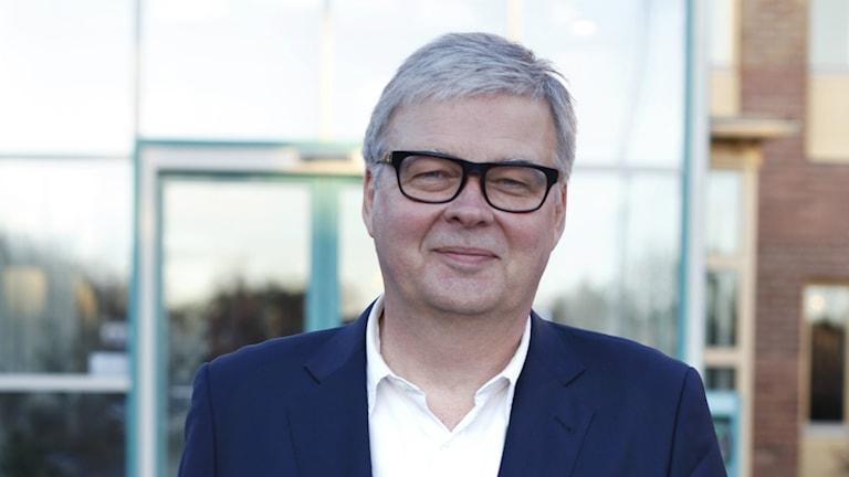Bengt Kjellson har grått, kort hår och glasögon med tjocka svarta bågar. Han är slätrakad och har på sig en kornblå kavaj över en vit skjorta med översta knappen uppknäppt. Han står framför en myndighetsbyggnad i rött tegel med glasentré. Foto: Katinka Igelberg