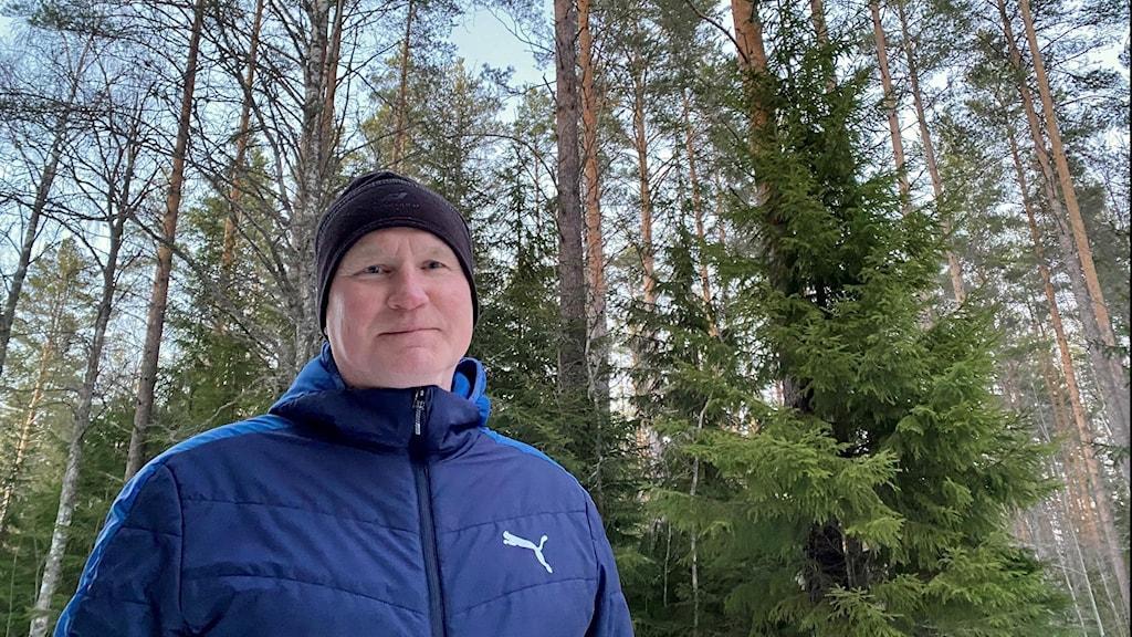 En man med blå jacka och svart mössa står i en skog och tittar in i kameran.