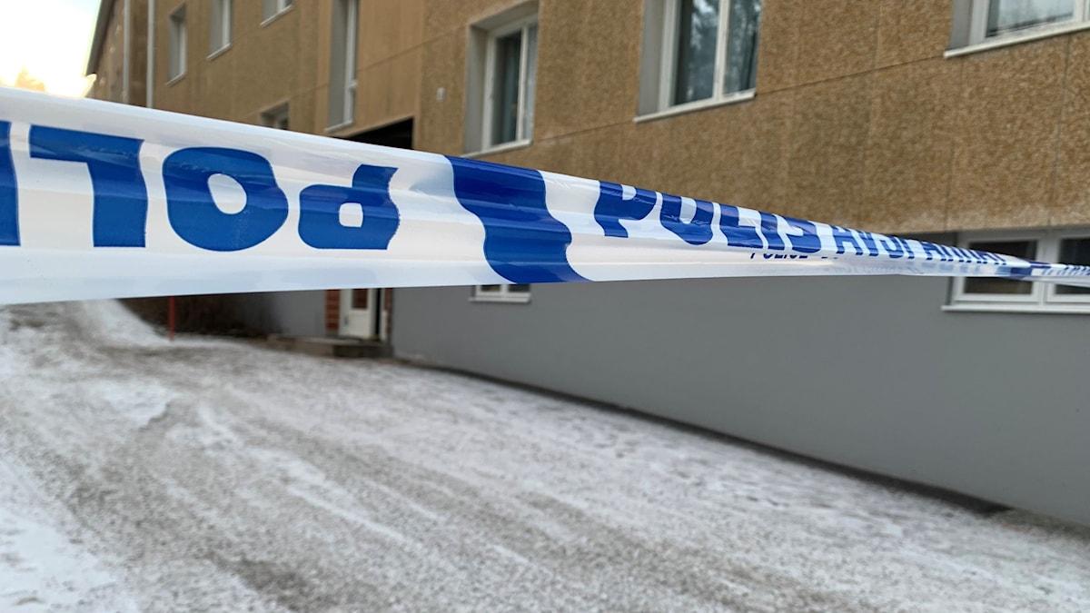 Polisens avspärrningsband och en hyresfastighet i bakgrunden.