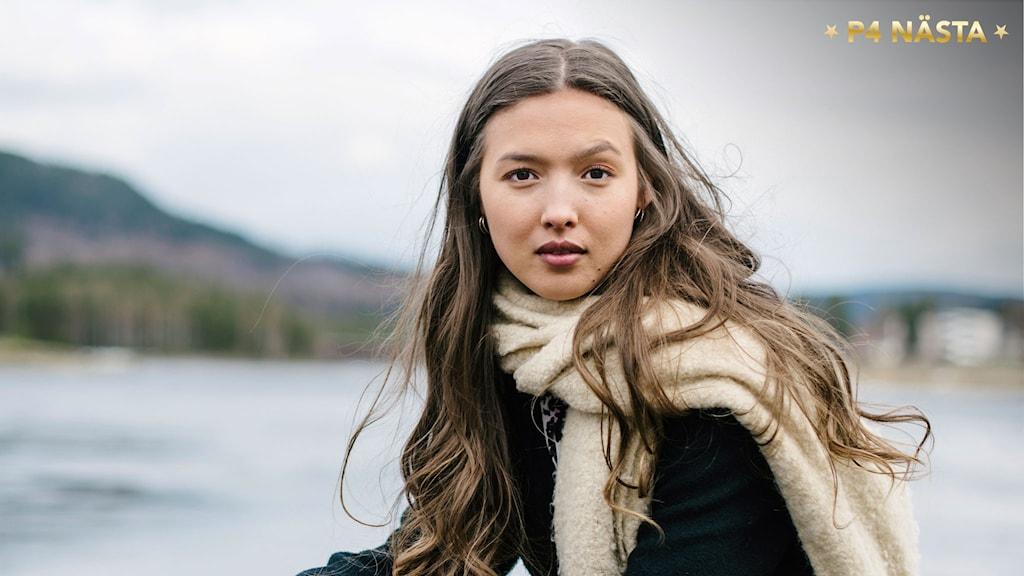 Amanda Heino. Hon tittar rakt in i kameran och i bakgrunden ser man en oskarp siluett av  Sollefteå med berg och bro. Foto: Petra Berggren/Sveriges Radio