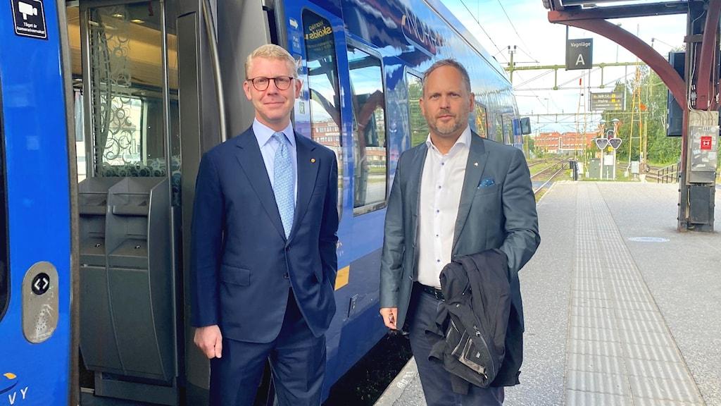 Kristoffer Tamsons (M), Trafikregionråd i region Stockholm och Jörgen Berglund (M), riksdagsledamot i Västernorrland står framför ingången på ett tåg. Foto: Tiffany Lind/Sveriges Radio