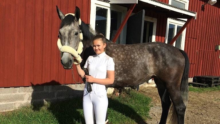 Wilma Lundgren står tillsammans med hästen Brita