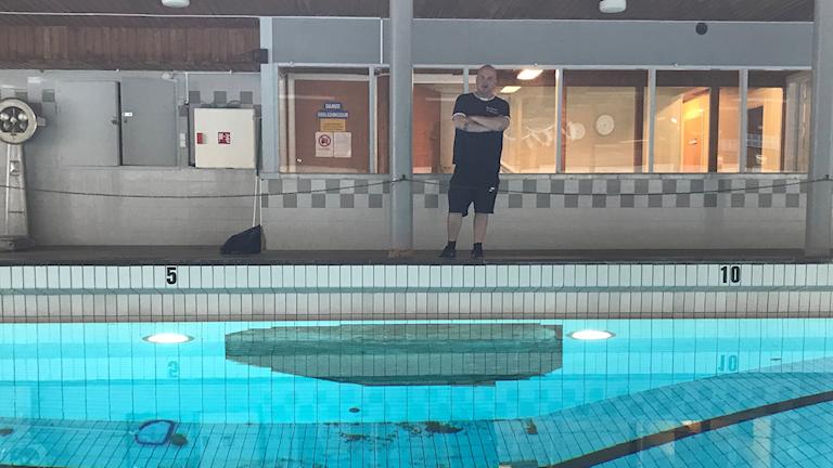 Man som står vid kanten av en simbassaäng med skadat kakel