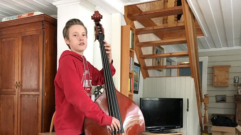 Gullik Strand spelar på sin bass i hemmet i Tennviken.