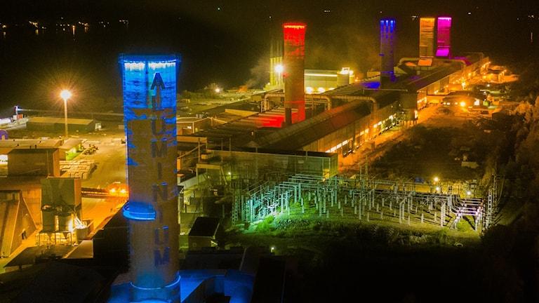 Skorstenarna på Kubal Aluminium lyser blått, rött, orange och rosa i den mörka natthimlen. Foto: Patrik Jonasson/PRIVAT