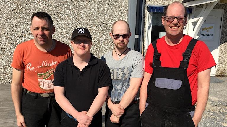 Fyra män står framför en husvägg i solen.