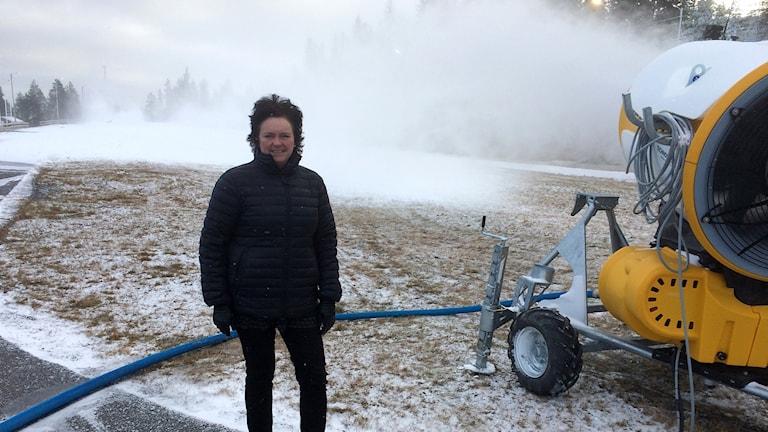 Anneli Solin från Sollefteå skidor står bredvid en snökanon som sprutar ut konstgjord snö. Foto: Lennart Sundwall/Sveriges Radio