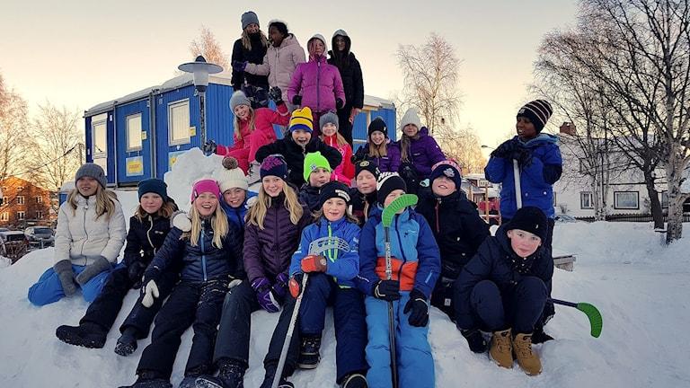 Klass 5 B Grön på Skönsmons skola sitter på ett snöberg på skolgården. Foto: Mari Burman