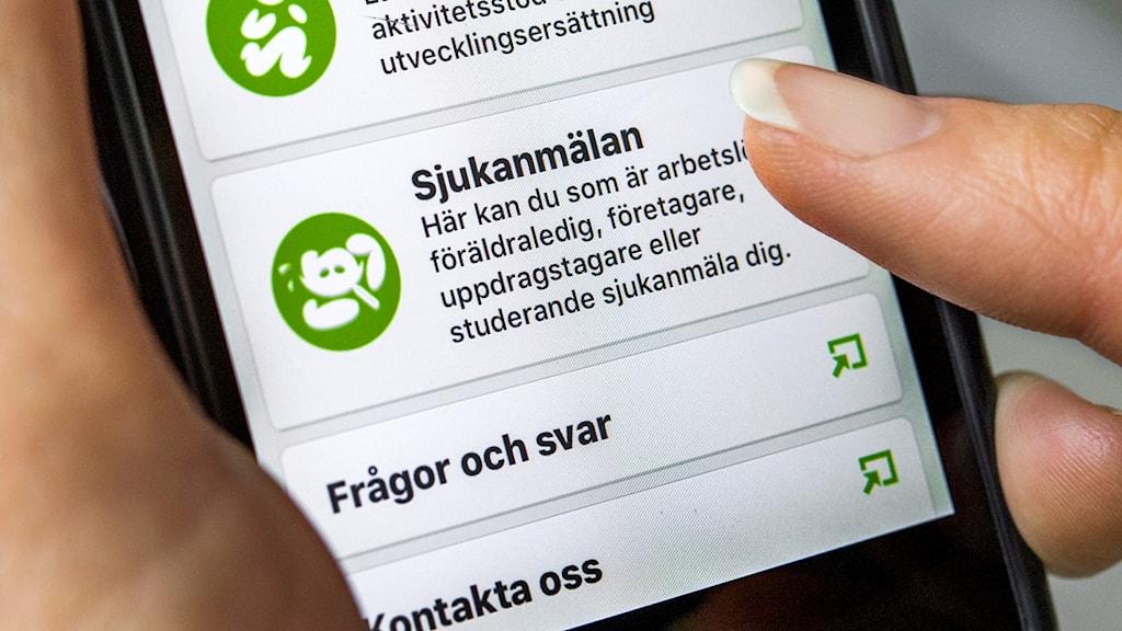 Person ska göra en sjukanmälan i sin mobil via försäkringskassans app. Foto: Claudio Bresciani/TT