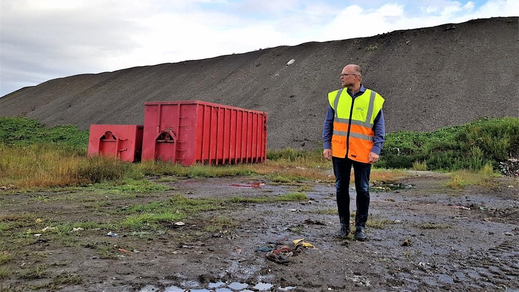 Bjarne Öberg i varselväst, fotad i helfigur, står framför en mycket stor hög av aska och slagg. Två öppna röda containrar syns också på bilden.