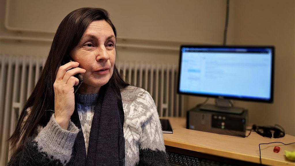 Lena Kroik med långt mörkt hår sitter med ryggen mot en datorskärm och pratar i telefon.