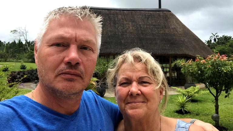 Christer och Karin Solgevik står i sin trädgård. Hus med bambutak i bakgrunden. Foto: Privat