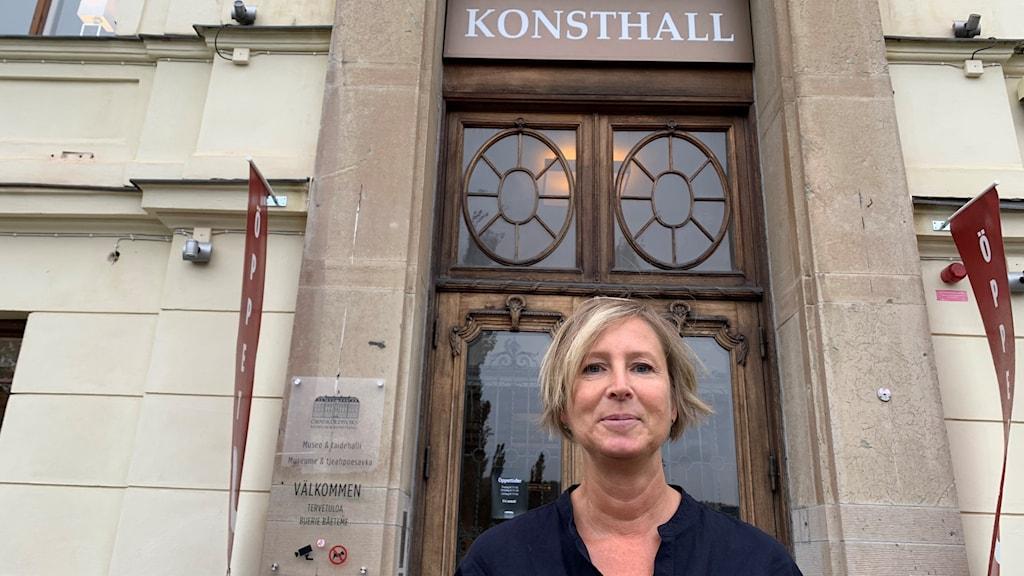 Kvinna som stör framför en pampig port, det står Konsthall