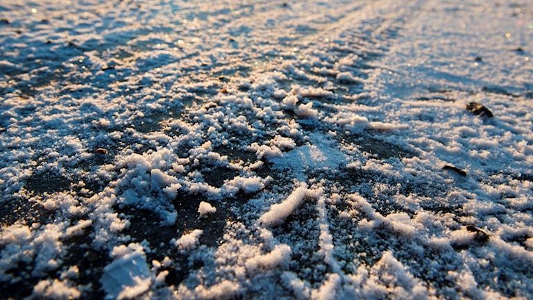 Is döljer sig under en tunt lager snö på en grusväg.