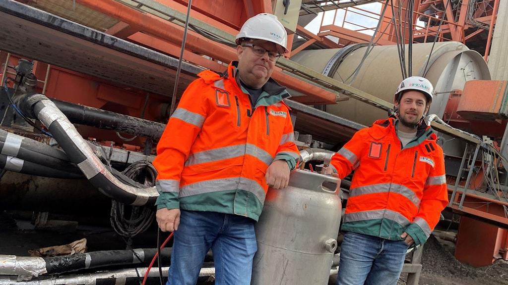 Två män i orangea arbetsjackor står framför en stor maskin med en cylinder mellan sig.