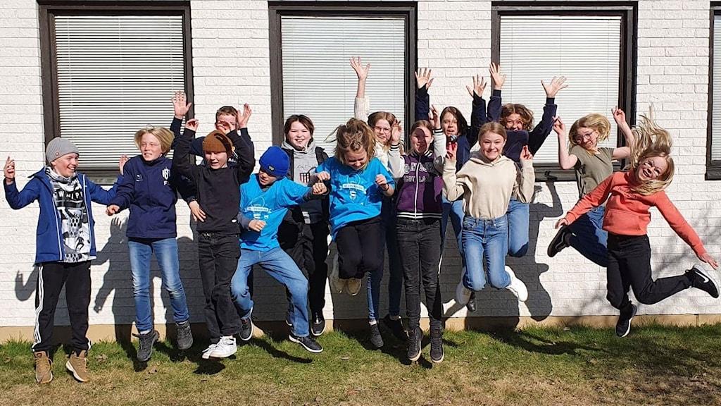 Eleverna i 5:2 på Mimerskolan hoppar glatt upp i luften ute vid den vita tegelfasaden på skolan. Foto: Ida Svensson