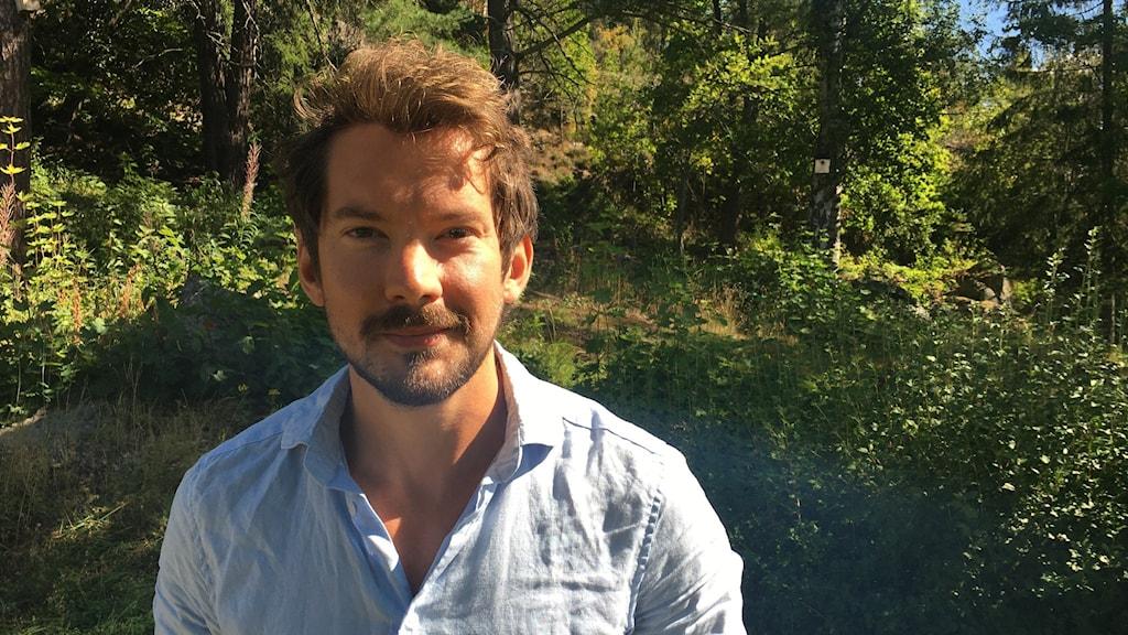 En av Region Västernorrlands folkhälsostrateger, Albin Dahlström, står framför ett lummigt grönområde. Han har på sig en ljusblå skjorta och tittar med vänlig blick in i kameran.